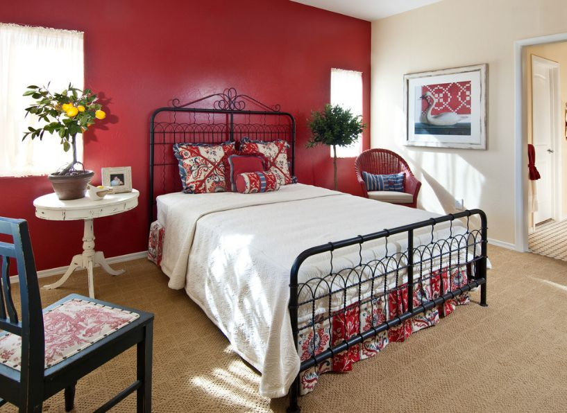 Freelancing - red wall and black iron frame for bed